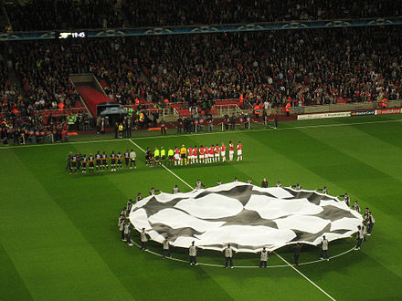 The Champions League anthem is played before the start of each match as the two teams are lined up while the Champions League logo is displayed in the centre circle. Beginning Arsenal Sevilla.jpg