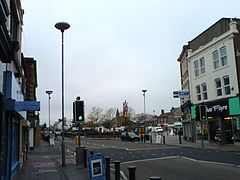 A road running off into the distance. On the right-hand side a three-storey building, with a shop front on the ground floor. Traffic lights and lamp standards are prominent. In the distance is the steeple of a church. The sky is grey.