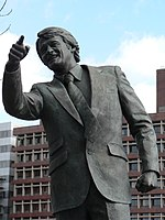 A bronze statue of a man in a suit, pointing with his right hand.