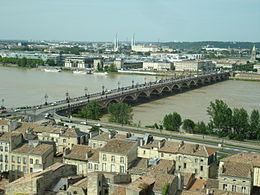 Un pont bas, muni d'une quinzaine d'arches, traverse un cours d'eau entre relie deux zones urbaines.