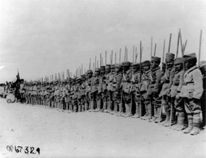 Hidden Armenians - A line of orphaned Armenian boys in military uniforms standing with sticks in Erzurum, September 1919.