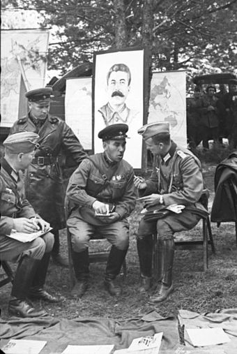 German and Soviet soldiers during the official transfer of Brest to Soviet control in front of picture of Stalin, in the aftermath of the invasion and partition of Poland by Nazi Germany and the Soviet Union in 1939. Bundesarchiv Bild 101I-121-0011-20, Polen, deutsch-sowjetische Siegesparade.jpg