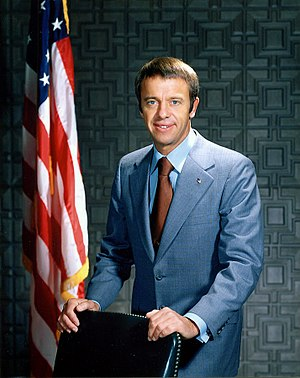 Shepard stands behind a chair wearing a blue suit. In the background is an American flag.