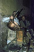 COLLECTIE TROPENMUSEUM Het gieten van gekookte suikerstroop in een mal tijdens de vervaardiging van suikerwerkfiguren voor mawlid an-nabi TMnr 20043347.jpg