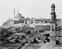 Uma mesquita multi-cúpula domina a murada Citadel, com túmulos em ruínas e um minarete solitário na frente.
