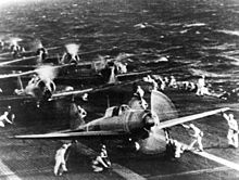 Planes on the deck of an aircraft carrier, with technical crews in white overalls attending the planes