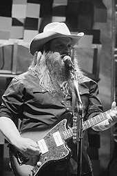 A man with long hair and a beard, wearing a cowboy hat, singing into a microphone and playing a guitar