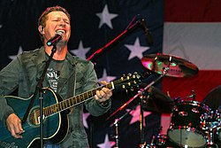 A dark-haired man playing a guitar and singing into a microphone in front of the American flag