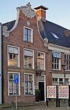 foto van Pand met verdieping onder zadeldak tegen klokgevel in de plaatselijke trant versierd met gebeeldhouwde aanzetkrullen, lijst en kuifstuk