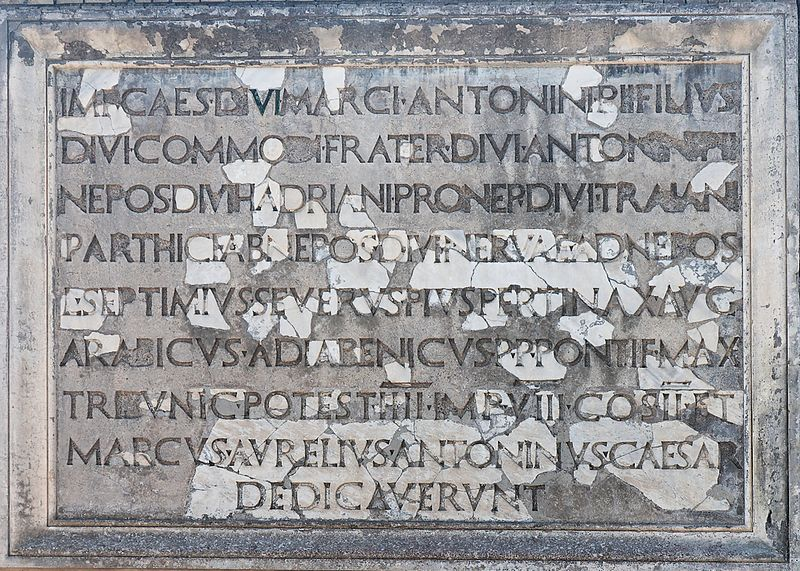 """Dedicated by the emperor Caesar, son of the divine Marcus Antoninus Pius, brother of the divine Commodus, grandson of the divine Antoninus Pius, great-grandson of the divine Hadrian, great-great-grandson of the divine Trajan, conqueror of Parthia, great-great-great-grandson of the divine Nerva, Lucius Septimius Severus Pius Pertinax Augustus Arabicus Adiabenicus, father of his country, Pontifex Maximus, holding the tribunician power for the fourth year, in the eighth year of his imperium, consul for the second time; and Marcus Aurelius Antoninus Caesar"" Dedicatory inscription Ostia Antica 2006-09-08.jpg"