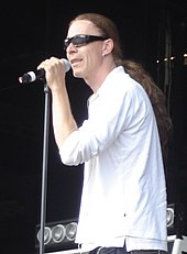 A picture of a man with long hair performing on stage with a microphone in his hand wearing sunglasses and a white top.