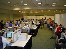 Large room, with reporters at computers in cubicles
