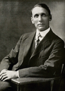 Black and white photograph of a man in an overcoat, sitting in a chair visible from the waist up. He is clean shaven, has his hair combed to the side. He wears a calm expression and is looking to the left towards the camera.