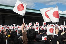 A group of people wave Japanese flags at a palace.