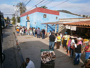 Bolivarian Revolution - Shoppers waiting in line at a Mercal store.