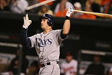 "A right-handed man in a grey baseball uniform reading ""Rays"" swings a baseball bat."