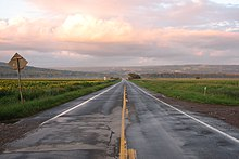 A two-lane paved road, wet in spots, stretching straight ahead with fields on either side towards a ridge in the distance. Above it in the sky is a cloud with orange-tinted sunlight on it; there is also a low mist over the fields in the distance.