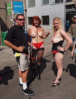 Dominance and submission - Animal roleplay: A dominant male holds two females using dog leashes, Folsom Street Fair, USA, 2010