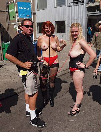Dominance and submission - A dominant male publicly holds two submissive females using leashes tied to their neck, Folsom Street Fair, 2010
