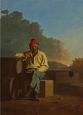 A man with graying hair and beard sits on a crate and leans against a barrel. He is wearing a red hat, white shirt, blue pants, and brown boots, and is smoking a pipe