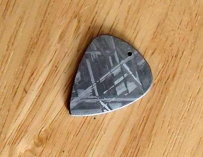 Gibeon meteorite made into a guitar pick. Acid...