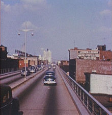 An elevated four lane freeway in an urban area as it appeared in 1954