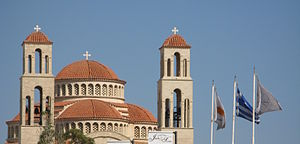 Constitution of Cyprus - Flags of Greece and Cyprus being flown on flagpoles with  cross finials in front of Agioi Anargyroi Church, Pafos.