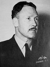 Portrait of moustachioed man in dark military uniform with pilot's wings on left pocket