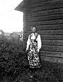 Helporträtt av en kvinna i folkdräkt vid ett hus - Nordiska Museet - NMA.0056411.jpg