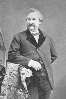 A monochrome photograph of a man from the thigh up, approximately 40 years old, with a large mustache and no sideburns, leaning with his right elbow on a fur-draped arm of furniture, looking slightly to the left