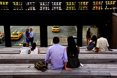 People sitting on wooden benches in a small amphitheater, which is elevated over a city street