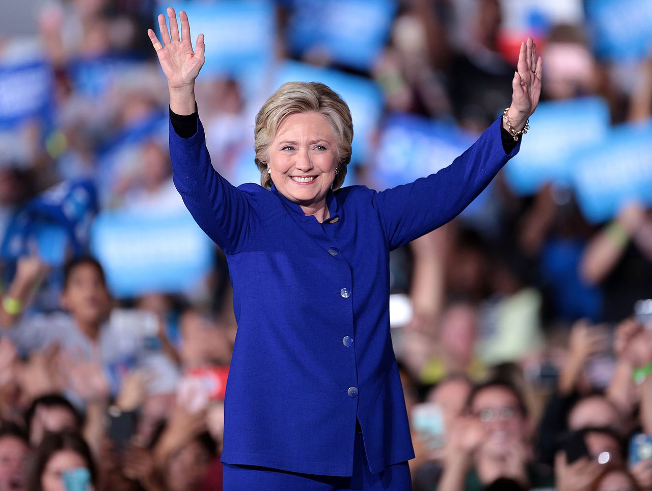 Clinton in a blue suit, looking toward the camera. Audience members in the background. She is at a speaking event in Tempe on November 2, 2016.