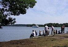 Photo de gens assis au bord d'un cours d'eau