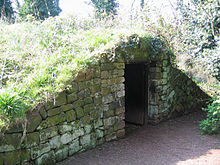 A mound-shaped structure covered in grass. At the front is a stone wall with a doorway.