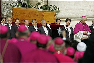 Funeral of Pope John Paul II - Borne on the shoulders of the Papal Gentlemen, the coffin of Pope John Paul II is taken from the altar for the Rite of Interment. Archbishop Piero Marini, then-Master of Pontifical Liturgical Ceremonies, preceded the casket.