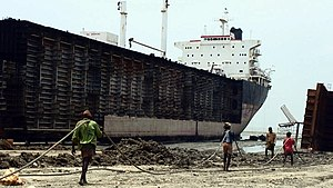 Ship breaking - Workers drag steel plate ashore from beached ships in Chittagong, Bangladesh