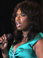 A black women with dark brown hair talking into a microphone. She is wearing a green satin dress with a with necklace.