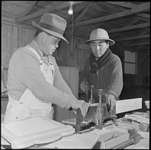 Photo of two incarcerated Japanese Americans using an adjustable mitre box.