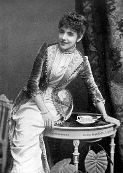 Full length shot of a young Bond, wearing Victorian clothes and curly hair up in a large bun
