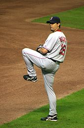 A man in a gray baseball uniform with red trim stands on a dirt-and-grass field with his left leg lifted. He is wearing a black baseball glove on his left hand, and looking over his left shoulder.