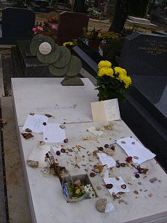 Marble grave stone with mementoes, flowers, notes and other small items placed on it.
