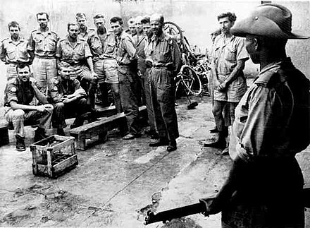 Katangese gendarme guards Swedish ONUC soldiers taken prisoner. Katangese gendarme with Swedish ONUC prisoners.jpg