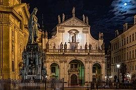 La façade d'une église baroque, de nuit, au clair de lune, entourée par plusieurs bâtiments, une statue d'un homme au premier plan à gauche.