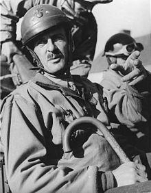 Un homme en uniforme avec une canne. Il porte un casque de l'armée française à l'ancienne avec une crête.