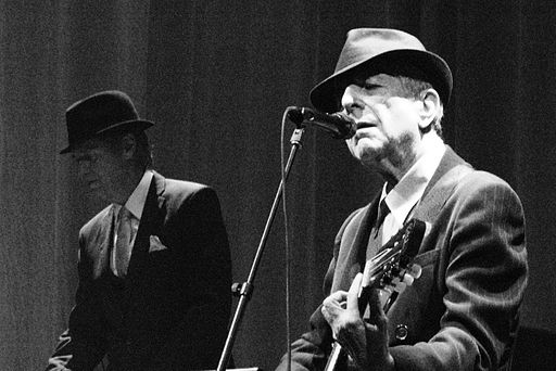 Photograph of an elderly pale-skinned man, wearing a suit and hat, singing into a microphone while playing a guitar.