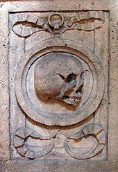 Close-up of a rectangular-shaped carving in stone. In the centre of the rectangle is a circle representing a mirror, and within the circle is a grinning skull. The circle is framed by ram's horns.