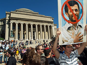 Protesters hold a sign showing Mahmoud Ahmadinejad who spoke at Columbia University on that day.