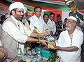 Mukhtar Abbas Naqvi distributing travel guide kit for Haj Pilgrims, at the flagging-off ceremony for 1st flight of Haj-2017, in Mumbai.jpg
