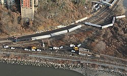 An aerial view of a wooded area between two watery areas in late autumn, with two railroad tracks forking to the top near the left and one following the water's edge. Several silvery train cars and a locomotive are lying on their sides off the tracks to the top; there are many parked yellow and white trucks and other vehicles between the two tracks.
