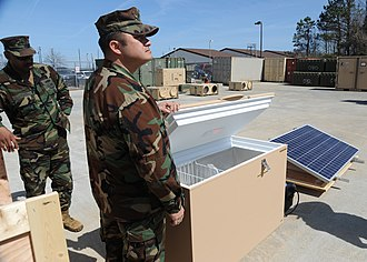 Solar-powered refrigerator - Naval Special Warfare support technicians receive training on a solar-powered refrigerator.
